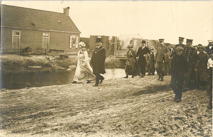 Koningin Wilhelmina, in gezelschap van burgemeester Albert Vriend van Odoorn, op weg naar de woning van Derk en Janneke van der Leij
