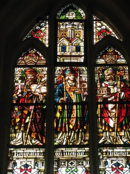 Glas-in-lood ramen in de kerk van Stade met vanaf links Bonifatius, Willehad en Ansgar. (Foto: Dirk Otten)