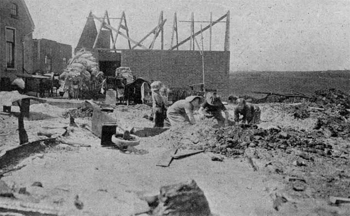 De bewoners van een verbrand huis te Valthermond tussen de puinhopen aan het zoeken, wat nog van waarde voor hen kan zijn.