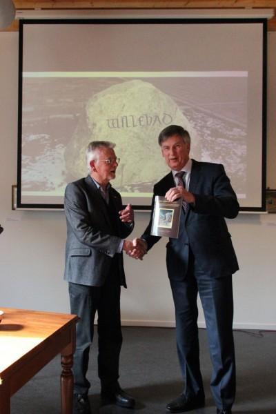 Dirk Otten reikt het eerste exemplaar van zijn boek Willehad uit aan gedeputeerde Cees Bijl.