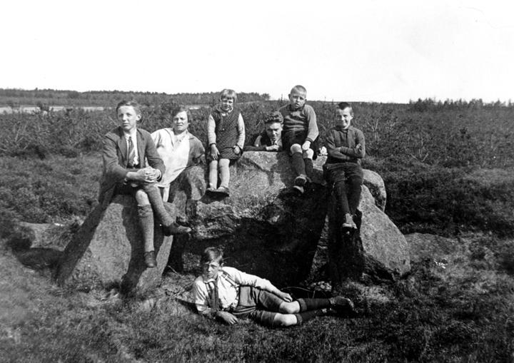 Hunebed Hunzebos (D31) rond 1925. Vanaf links: Steven Meelker, Roelfien Smit-Segen, Hillechien Stevens, Jannes Waldhuis, Albert Smit, Albert Stevens en liggend Geert Meelker. (Gemeentearchief Borger-Odoorn)