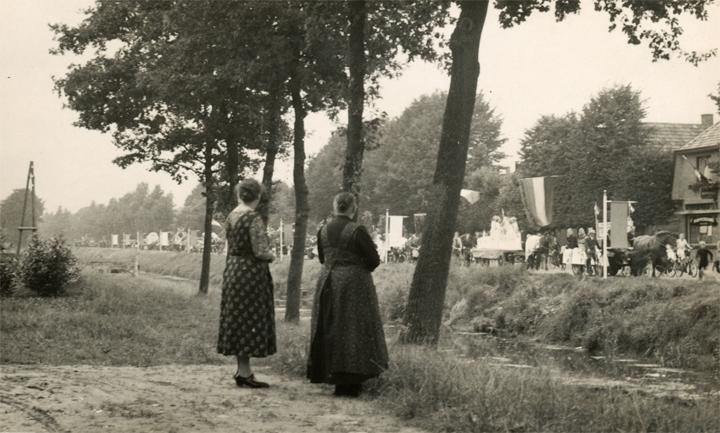 De dames Mensing bekijken in 1963 de optocht in de Havenstraat bij de viering van het honderdjarig bestaan van Erica. Voor hen de versmalde Veenschapswijk. (Foto Historische Kring Erica)