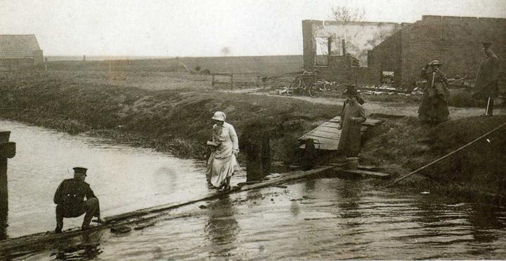 Zonder aarzelen stapte de koningin over de smalle planken die op de plaats van de verbrande vonders over het kanaal waren gelegd. (Collectie Roelof Boelens)