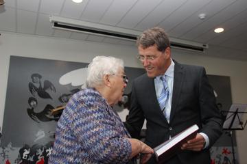 Burgemeester Eric van Oosterhout overhandigt het eerste exemplaar aan de 88-jarige Jantje Jonkers-Derks, de oudste inwoner van Noordbarge.
